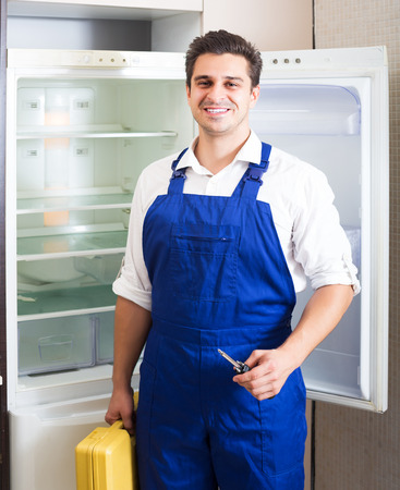 refrigerator kitchen: Smiling handyman repairing refrigerator in domestic kitchen
