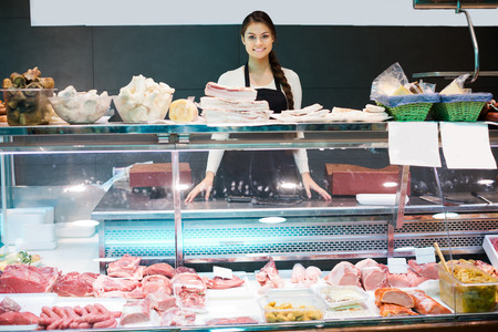 shopgirl: Female butcher with lard and meat in counter of store