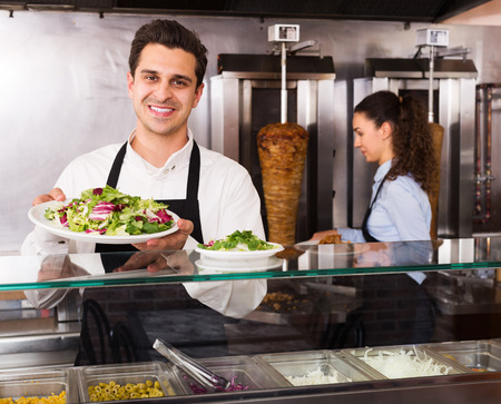 restaurant staff: Young attrective restaurant staff posing at kebab counter and smiling