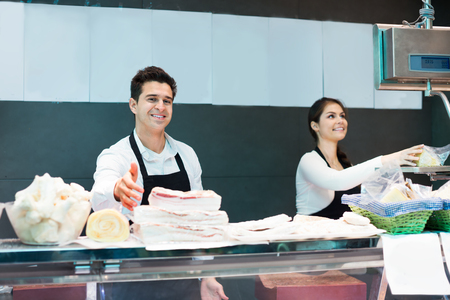 salo: Delicatessen store staff selling fresh-killed a meat and salo
