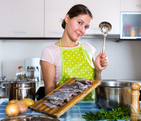 loathsome: Cheerful housewife trying new recipe of sprattus in kitchen