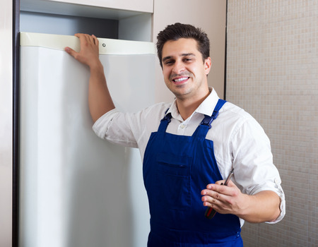 refrigerator kitchen: Happy young handyman repairing refrigerator in domestic kitchen