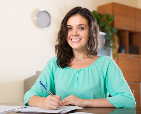 filling in: Cheerful smiling young brunette long-haired woman filling in paper at home