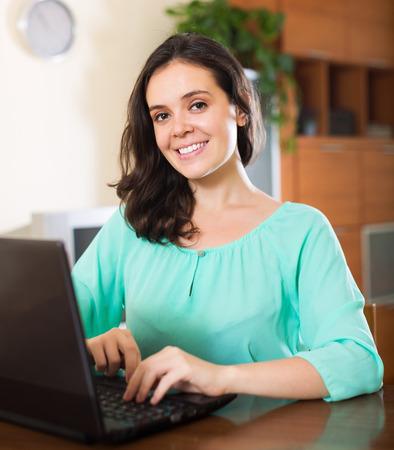 netbook: Smiling woman looking at netbook in living room