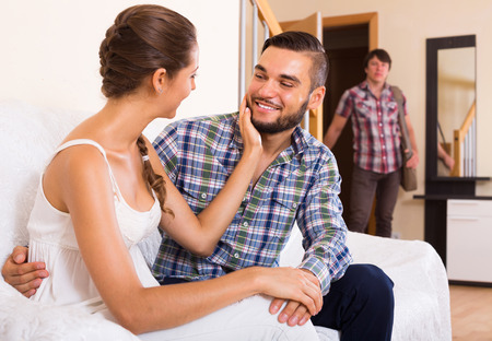 coming home: Surprised young spouse coming home in wrong moment Stock Photo