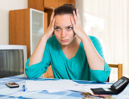financial problems: Young woman sitting depressed at the table because of financial problems