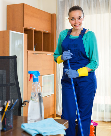 office cleanup: Young smiling female cleaner in uniform washing the floor at office