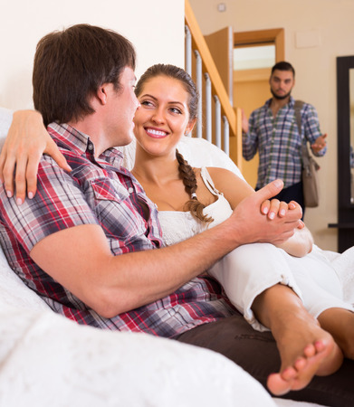 unfaithfulness: Surprised guy discovering his cheating young attractive wife at home