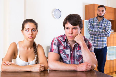 bisexual women: Three sad young adults at home: problems of love triangle Stock Photo