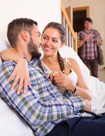 polygamy: Young adult discovering his cheating attractive young wife at home Stock Photo