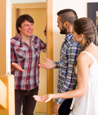 mate married: Happy male guest saying hello to friends on the threshold. Focus on the man Stock Photo