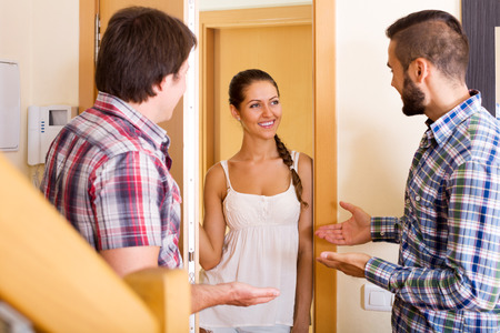 Smiling guest saying hello to friends on the threshold. Focus on the woman Stock Photo