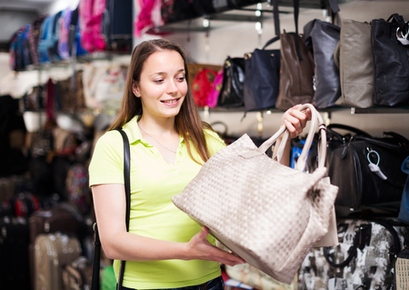 leather bag: Happy woman choosing leather bag in shop