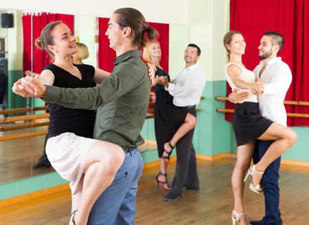 merry dancers: Group of people having fun while dancing tango