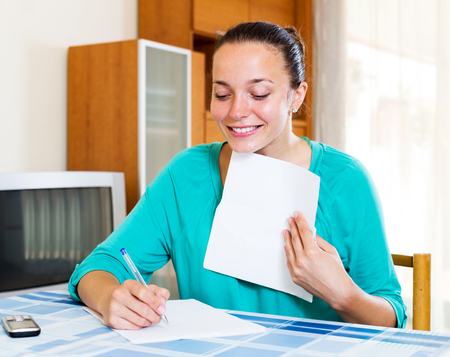filling out: Happy girl filling out tax forms while sitting at her desk Stock Photo