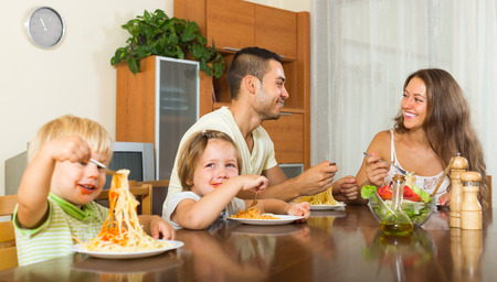 gladful: Happy smiling family of four eating with spaghetti at table. Focus on man