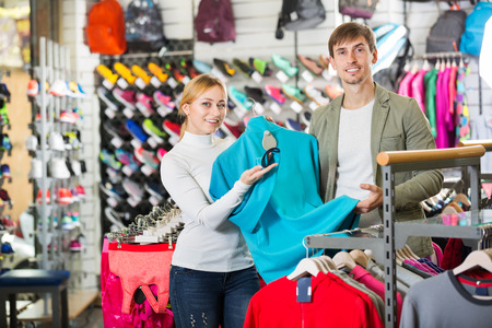 fitting in: Young man and woman choosing and fitting a clothing in sport department. Focus on both persons
