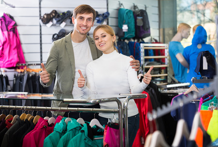 fitting in: Young man and beautiful woman choosing and fitting clothing in sport department. Focus on both persons