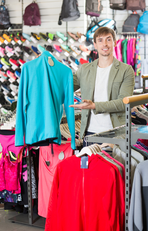 warm jacket: Smiling man selecting a warm jacket in the sport department