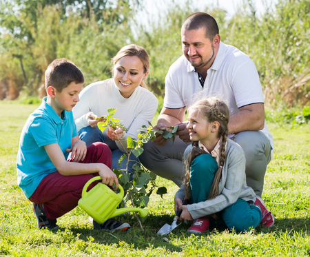 planting a tree: Cheerful young parents with two children planting a tree and watering it together Stock Photo