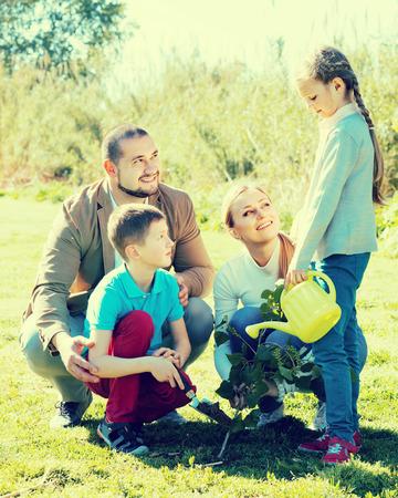 sembrando un arbol: Sonriendo familia de cuatro plantar un �rbol en el jard�n en un clima soleado Foto de archivo