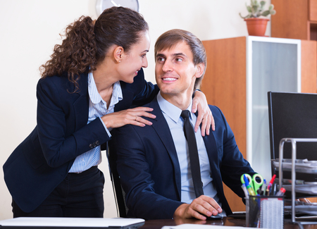 molestation: Sexual harassment in office: female boss flirting with employee and smiling