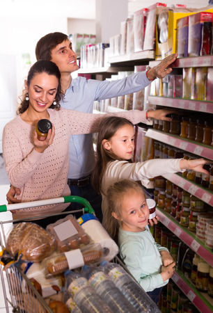 4s: Happy parents with children choosing jar of confiture in store