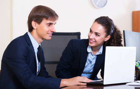 yuppie: Happy office colleagues successfully working together indoors and smiling