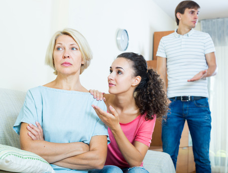 trying: Frustrated woman watching how adults trying to reconcile with her Stock Photo