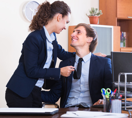 molestation: Sexual harassment in office: smiling female boss flirting with employee at workplace Stock Photo