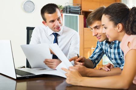 spouses: Happy young spouses and serious salesman with documents at agency