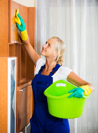 cleanup: Professional positive female cleaner doing regular clean-up in home interior
