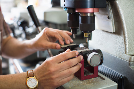 Professional skilful key cutter making door keys copies in locksmith Standard-Bild