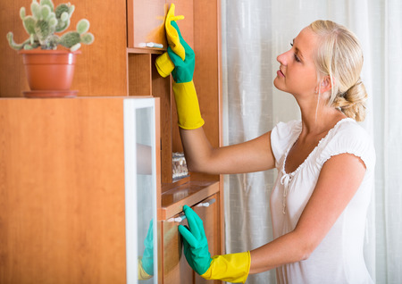 dusting: Young housewife in rubber gloves dusting furniture at home Stock Photo