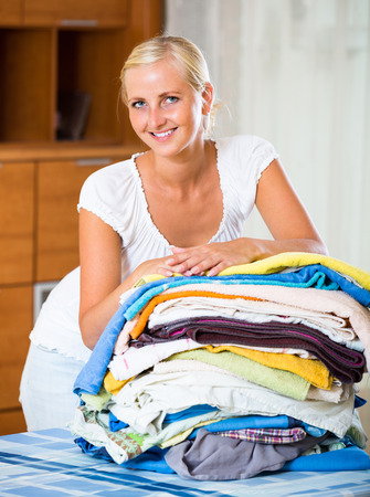 sorting: Cheerful smiling young blonde woman sorting out laundry at home Stock Photo