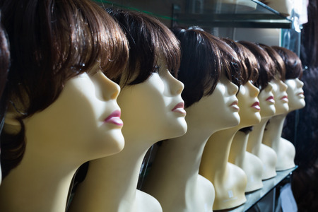 peruke: Mannequins with brunet style wigs on shelves of hair salon Stock Photo