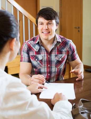 private insurance: Young man discussing details of private insurance with agent in home interior