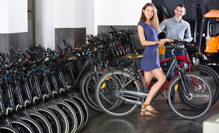 rental agency: Happy young couple selecting a bikes in a rental agency indoors. Focus on women