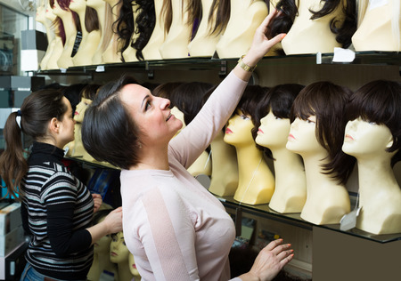 peruke: russian female buyers discussing synthetic and natural hair perukes at store