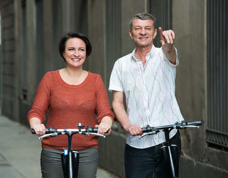 staying: Mature happy couple staying with electric bikes outside and smiling. Focus on man