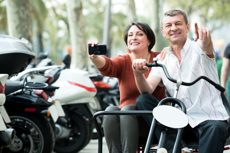 adulthood: Mature man and woman traveling through city by twin  bicycle Stock Photo