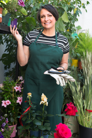 selling service smile: Friendly smiling female florist  in apron holding horticultural tools in flower shop