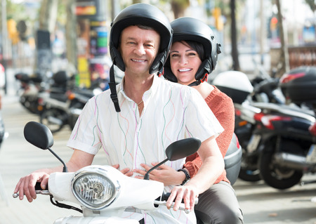 adulthood: Positive man and woman traveling through city by scooter