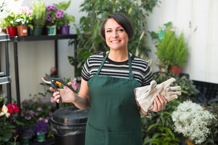 horticultural: Smiling female florist in apron holding horticultural tools in gardening store Stock Photo