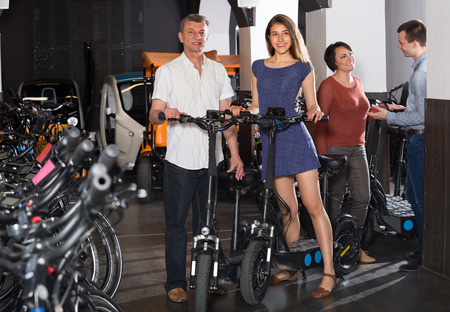rental agency: Happy family of four selecting electric bikes at rental agency indoors. Selective focus