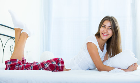 Happy female teenager with long hair relaxing in bed