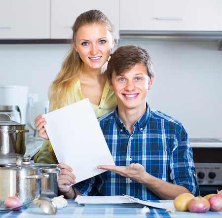middle joint: Young spouses filling forms for investment papers in domestic kitchen