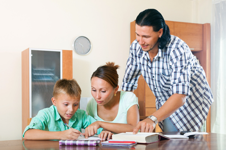 capable of learning: Ordinary family of three doing homework in home interior