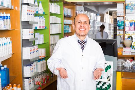 overall: Joyful male pharmacist in white overall posing in drugstore