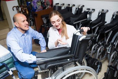 orthopaedic: Smiling  female consultant offering manual wheelchairs to male customer in orthopaedic store